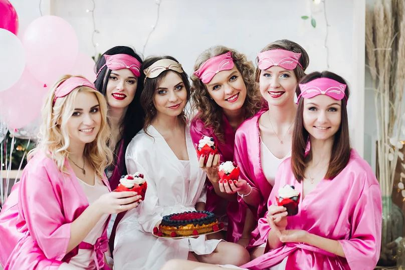 Girls at a bachelorette party with silk robes on. They are baking for the bachelorette party.