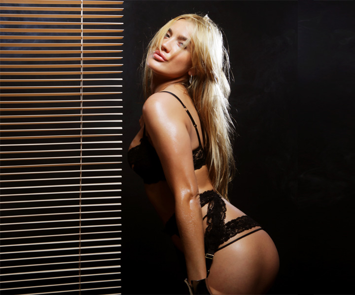A sexy blonde female stripper in lace underwear and in a sexy pose with ass sticking out
