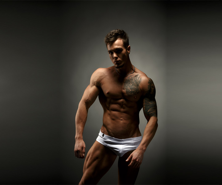 A male stripper for hire without a shirt on and a pair of white bikini underwear on