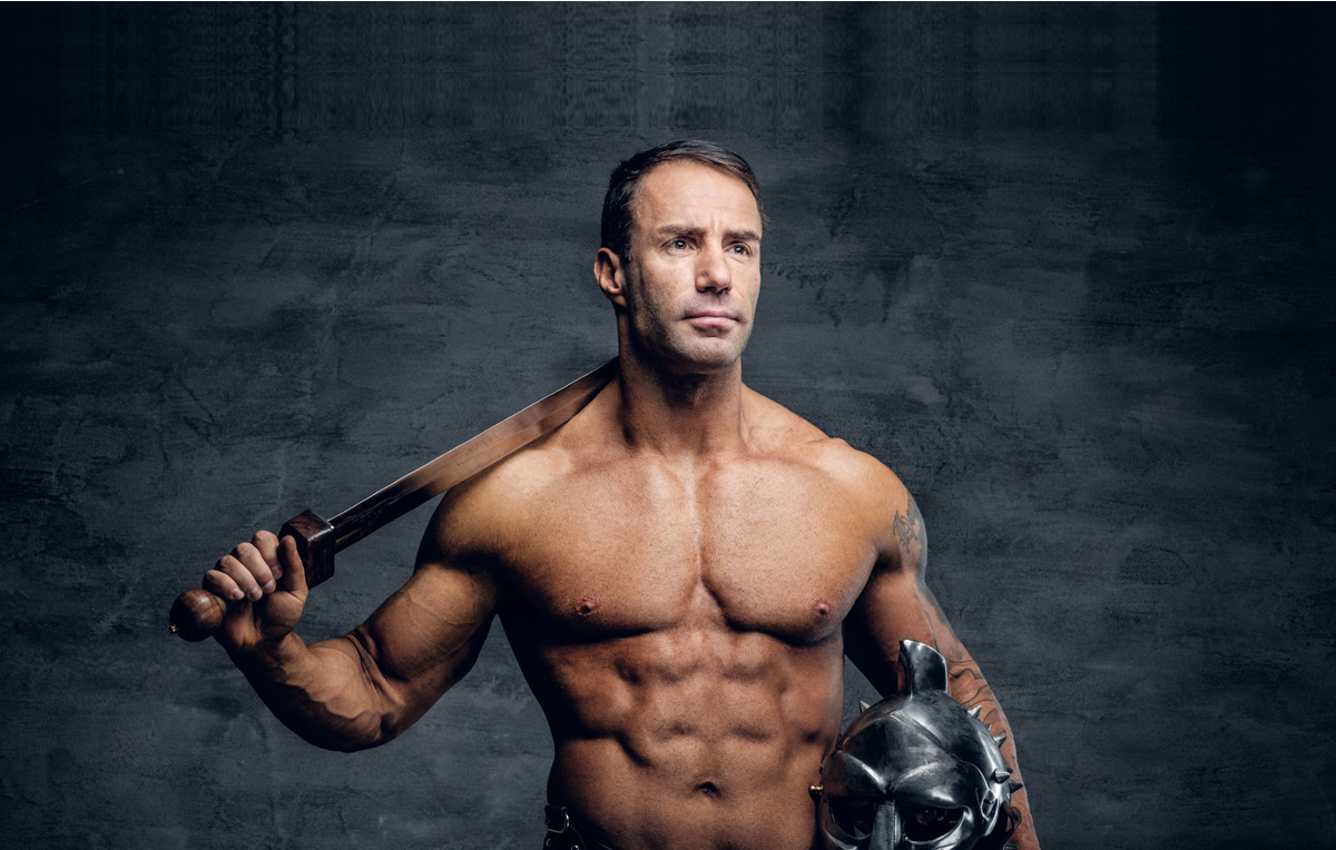 Male stripper without a shirt and with a helmet and sword