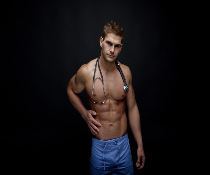 Sexy male stripper without a shirt in scrubs with a stethoscope around his neck