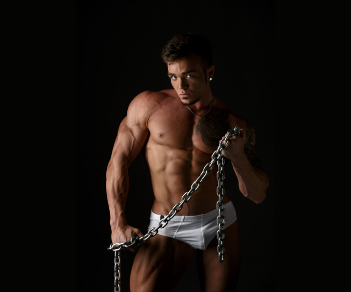 A ripped male stripper without a shirt and a small white bikini underwear on holding a chain