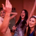 Girls partying and having a great time with a male stripper for a bachelorette party.